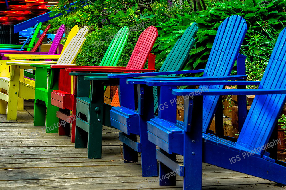 A row of brightly painted Adirondack Chairs on the dock at Key Bridge Boat Club Georgetown,Washington DC