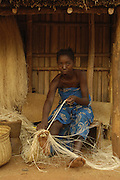 Sakalava woman working with Raffia from the Raffia palm (Raffia rarinifera) The fibres are combed out from the leaves once the leaves have dried.  They are either left their natural colour or dyed with various natural dyes. These are then woven into hats, baskets and mats that are very characteristic of Madagascar. There is a project in the Ankarafantsika Nature Reserve helping several local communities to sustainably yield the palm leaves and thereby make a living from the forest and earn money rather than live off the forest causing more habitat distruction.<br />Ankarafantsika Nature Reserve, Western deciduous forest. MADAGASCAR