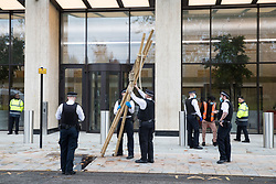 London, UK. 10 November, 2020. Metropolitan Police officers remove a tripod used by environmental activists from Extinction Rebellion outside the Shell Centre for an event to mark the 25th anniversary of the killings of the Ogoni Nine. The Ogoni Nine, leaders of the Movement for the Survival of the Ogoni People (MOSOP), were executed by the Nigerian government in 1995 after having led a series of peaceful marches involving an estimated 300,000 Ogoni people against the environmental degradation of the land and waters of Ogoniland by Shell and to demand both a share of oil revenue and greater political autonomy.