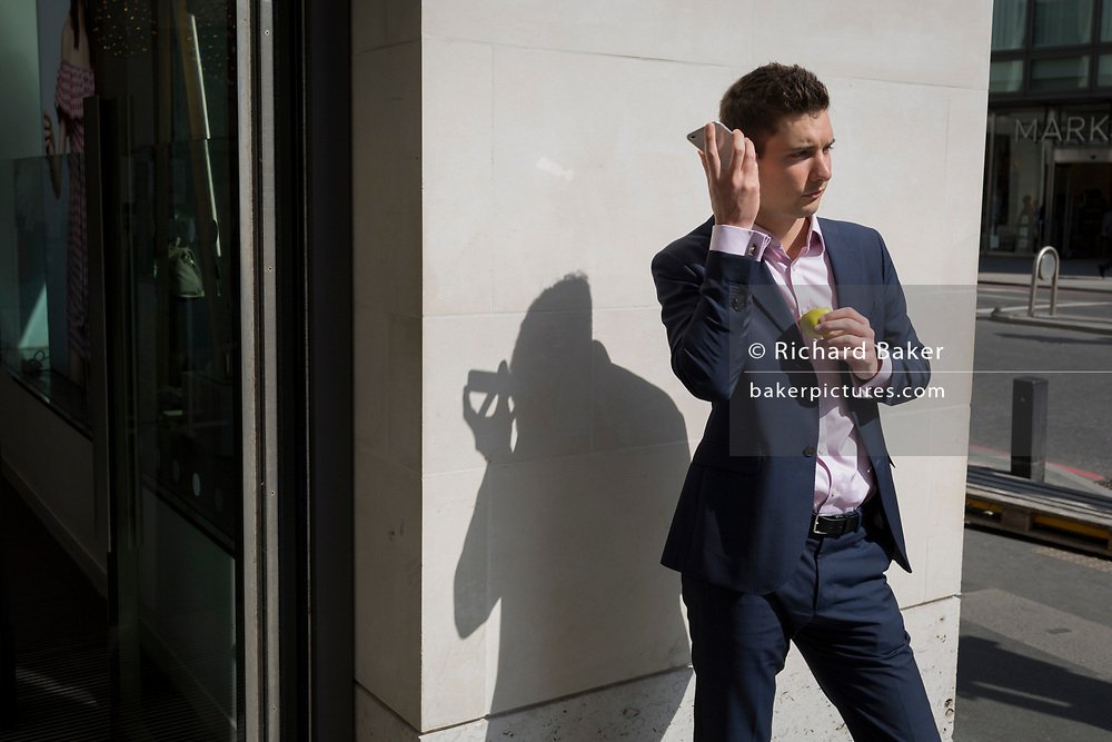 A young man listens to his phone in the City of London, the capital's financial district also known as the Square Mile, on 6th April 2017, in London, England.