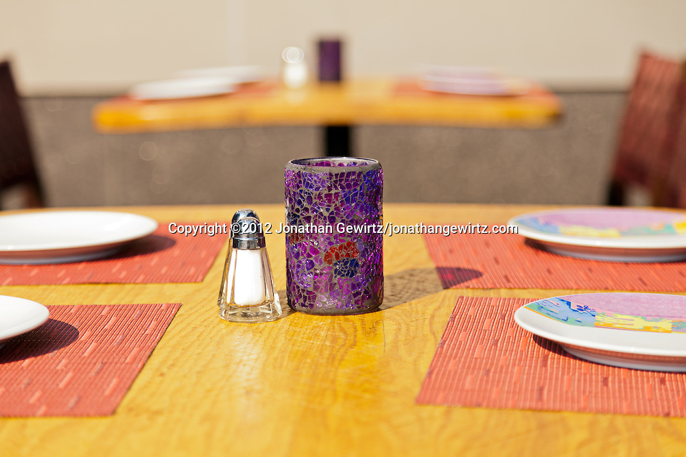 Tables and place settings in a brightly lit casual outdoor restaurant. WATERMARKS WILL NOT APPEAR ON PRINTS OR LICENSED IMAGES.
