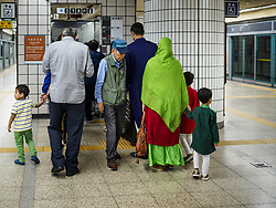 June 15, 2018 - Seoul, Gyeonggi, South Korea - A Muslim family waits to get an elevator in Itaewon Subway Station on their way to Seoul Central Mosque on Eid al Fitr, the Muslim Holy Day that marks the end of the Holy Month of Ramadan. There are fewer than 100,000 Korean Muslims, but there is a large community of Muslim immigrants in South Korea, most in Seoul. Thousands of people attend Eid services at Seoul Central Mosque, the largest mosque in South Korea. (Credit Image: © Jack Kurtz via ZUMA Wire)