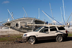 03 Oct, 2005.  New Orleans, Louisiana.  Hurricane Katrina aftermath.<br /> Smashed yachts at the Southern Yacht Club on the shores of Lake Pontchatrain in Lakeshore, New Orleans. Yacht meets car. An insurance headache.<br /> Photo; ©Charlie Varley/varleypix.com