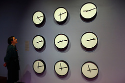 """© Licensed to London News Pictures. 17/10/2019. LONDON, UK. A staff member views """"Timepieces (Solar System)"""", 2014, by Katie Paterson, an installation showing the time on the nine planets in the solar system and the moon. Preview of """"Moving to Mars"""" at the Design Museum. The exhibition explores how sending humans to Mars is a frontier for science as well as design and features over 200 exhibits from NASA, the European Space Agency together with new commissions.  The show is open 18 October to 23 February 2020.  Photo credit: Stephen Chung/LNP"""