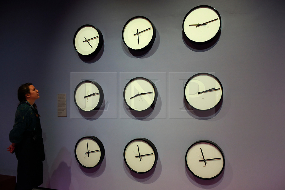 "© Licensed to London News Pictures. 17/10/2019. LONDON, UK. A staff member views ""Timepieces (Solar System)"", 2014, by Katie Paterson, an installation showing the time on the nine planets in the solar system and the moon. Preview of ""Moving to Mars"" at the Design Museum. The exhibition explores how sending humans to Mars is a frontier for science as well as design and features over 200 exhibits from NASA, the European Space Agency together with new commissions.  The show is open 18 October to 23 February 2020.  Photo credit: Stephen Chung/LNP"