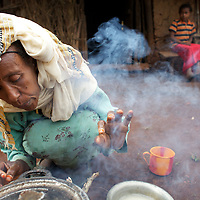 Belaynesh cooks breakfast for her neice (looking on) and herself outside their home in the village of Amba Zetegn. <br /> <br /> Belaynesh Hussen (age 50) lives with her niece Tsehaynesh Bistegn, age 10, in a thatched house in Amba Zetegn, 20km from Assosa town. She farms sorghum, maize, teff and soya, all sold through the local farmers co-operative society of which she has been a part for the past three years. This village co-op is affiliated to the Assosa Farmers Multipurpose Cooperative Union.<br /> <br /> Growing oil seeds presents challenges for the famers of Assosa in western Ethiopia. Many of the most vulnerable are forced to sell to when they cannot be guaranteed a good price for their product. Farms are often located in isolated areas which entails huge amounts of time and effort simply getting seeds to market. Many farmers do not have the resources to properly invest in their land and are tied into exploitative loan arrangements with brokers that deny them the chance to take proper control of their farms. And, as with other agricultural products, it is those agents that process the seeds into oil that secure the greatest profit, very little of which trickles down to benefit the farmer.<br /> <br /> In response to these pressures, twenty farming cooperatives have formed the Assosa Farmers Multipurpose Cooperative Union. By working together, individual farmers are able to pool their resources and squeeze out exploitative agents and brokers. The Union has sufficient capital that it can afford to wait for prices to reach a level at which it is profitable to sell seeds to market. The Union provides loans to constituent members together with training and advice to help farmers make better use of their land. And by collectively hiring vehicles through the Union, farmers need not spend so much time ferrying their produce to market. <br /> <br /> All these measures benefit farmers and have now provided the Assosa Farmers Multipurpose Cooperative Union the confidence to establish an oil-seed processing unit in th