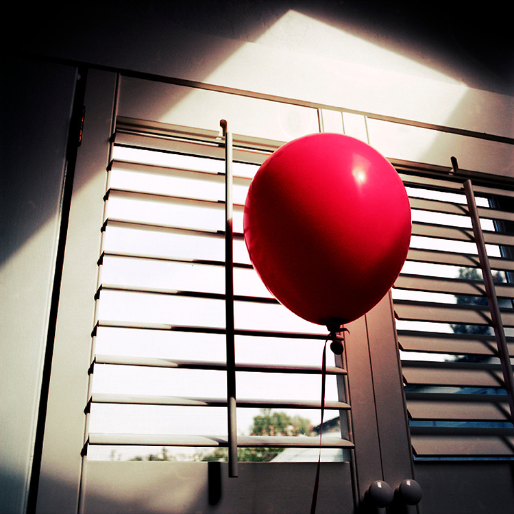A red balloon floating by a closed louver shutter in strong sunlight. The light in the shape of a rectangle.