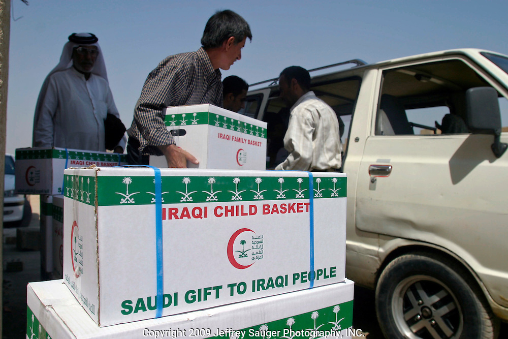 Emergency aid packages for poor people are distributed at the Community of Leaders and Chiefs for Iraqi Tribes in Baghdad, Iraq, Thursday, August 7, 2003. Each sheik, or chief of the their tribe, gets 15 boxes of aid for the poor. For many Iraqis, the community is the only place they can go to receive dependable aid.The community receives the aid packages from Saudi Arabia.
