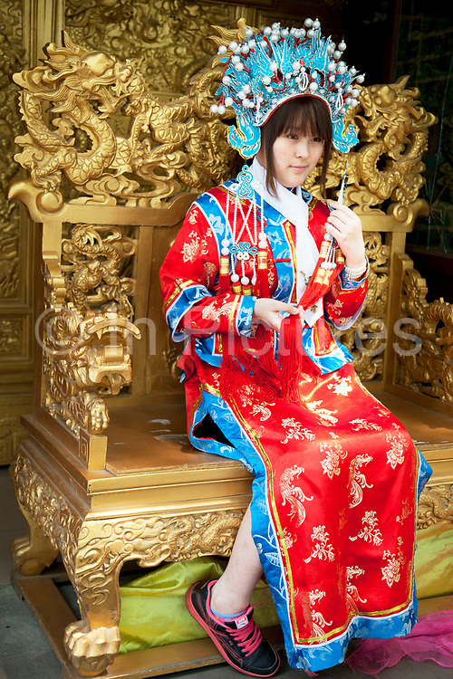 Girl sitting in a golden throne has her photo taken wearing traditional Chinese clothing. Beihai Park is an imperial garden in Beijing. First built in the 10th century, it is amongst the largest of Chinese gardens, and contains numerous historically important structures, palaces and temples. Since 1925, the place has been open to the public as a park. It is also connected at the south to the Shichahai. The Park has an area of more than 69 hectares, with a lake that covers more than half of the entire Park.