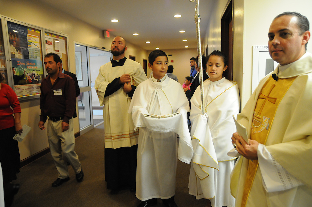Alter servers Antonio Rivera,13, and Miriam Castro, 16, await holding a mitre and crosier for Bishop George Rassas, (not seen) who will formally install Fr. Claudio Diaz (right) as Pastor of Mision San Juan Diego in Arlington Heights.