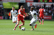Southampton's Adam Lallana © breaks past Swansea's Dwight Tiendalli. Barclays Premier league match, Swansea city v Southampton at the Liberty stadium in Swansea, South Wales on Saturday 3rd May 2014.<br /> pic by Andrew Orchard, Andrew Orchard sports photography.
