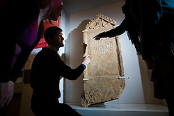 """© Licensed to London News Pictures 25/01/2016, Cirencester, UK. Collections officer James Harris (2L) looks at a unique Roman tombstone, found in February 2015, here on display for the first time at Corinium Museum in Cirencester. The tombstone was found near skeletal remains thought to belong to the person named on its inscription, making the discovery unique. After being found during excavation works on a former site of a garage, archaeologists said they believed it marked the grave of a 27-year-old woman called Bodica. Other theories point to it possibly belonging to a couple - as skeletal remains of women were found nearby.<br /> The inscription reads """"To the shades of the dead, Bodicacia spouse lived 27 years"""". Photo Credit : Stephen Shepherd/LNP"""