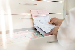 Male doctor reading the index card of a patient by drawers, Munich, Bavaria, Germany