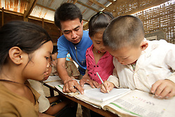 A group of children including Keo, 7 yrs old, the girl with brown T-shirt and Puiey, 9 yrs old working together with their teacher Khamonh Ulaythong, 28 yrs  and other unnamed children, Vang Mak primary school, Vieng thong district, Bolikhamxai Province, Lao PDR