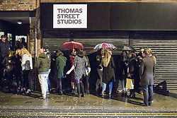 """© Licensed to London News Pictures . 19/12/2014 . Manchester , UK . People queue beneath umbrellas as they wait to enter a club on Thomas Street . """" Mad Friday """" revellers out in the rain and cold in Manchester . Mad Friday is typically the busiest day of the year for emergency services , taking place on the last Friday before Christmas when office Christmas parties and Christmas revellers enjoy a night out .  Photo credit : Joel Goodman/LNP"""