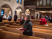"""15 MARCH 2020 - DES MOINES, IOWA: A woman by herself during Sunday services in St. John's Lutheran Church in Des Moines. Attendance at St. John's was about ⅔ below normal for a Lenten Sunday. Most churches in the Des Moines area canceled their Sunday services or switched to an online service this week. Those churches that conducted Sunday services imposed """"social distancing"""" guidelines, including no physical contact, and had significantly lower attendance. The Governor of Iowa announced Saturday night that the Coronavirus in Iowa had entered the """"community spread"""" phase when a person in Dallas County, in the Des Moines metropolitan area, tested positive for Coronavirus. This is the first reported case in the Des Moines area. As of Sunday morning, Iowa was reporting 18 people tested positive for Coronavirus.          PHOTO BY JACK KURTZ"""
