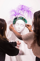 """© Licensed to London News Pictures. 05/04/2019. LONDON, UK. Gallery assistants check a creation at """"The Great Hat Exhibition - World Garden"""", which is taking place at the Menier Gallery near London Bridge until 12 April 2019, as part of London Hat Week.  150 international milliners have created 200 hats inspired by the colours, flowers, plants and landscapes from around the world.  The exhibition is curated by Monique Lee Millinery and supported by X Terrace, a fashion platform.  Photo credit: Stephen Chung/LNP"""
