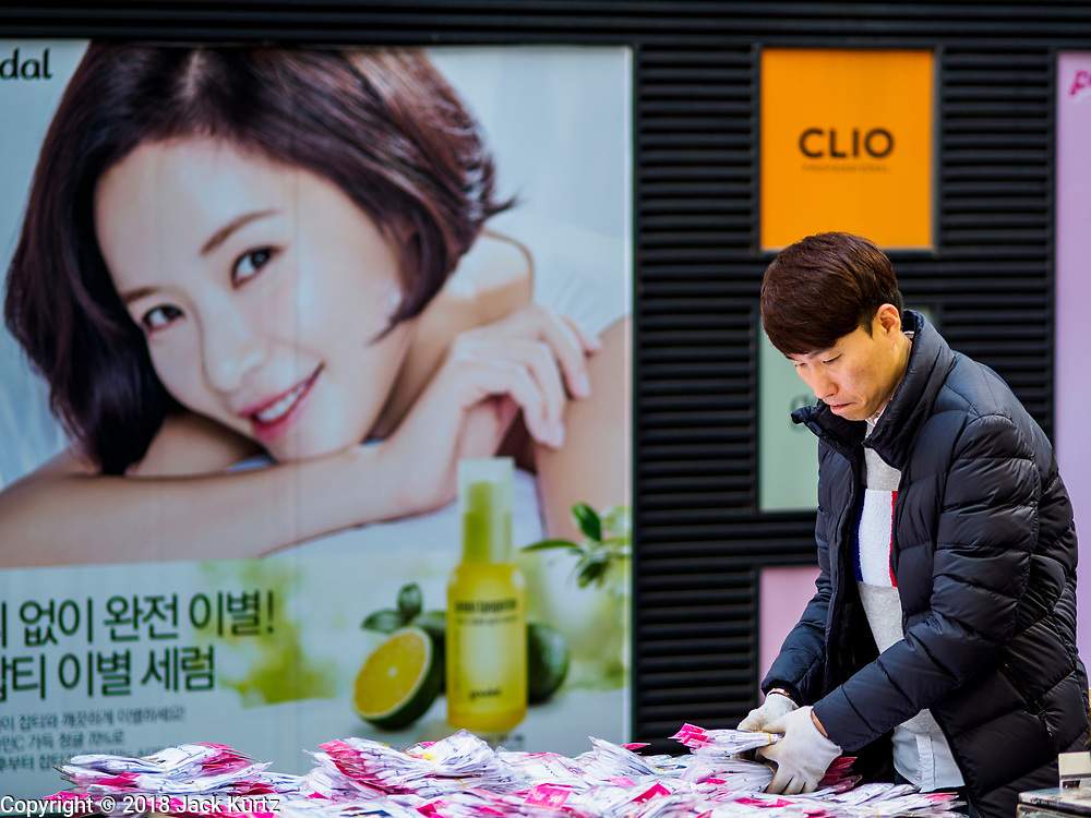 14 OCTOBER 2018 - SEOUL, SOUTH KOREA: A vender sets up his stand selling K-pop memorabilia in front of a cosmetics shop in the neighborhood around Myeongdong Street between the Cathedral and City Hall in Seoul. It's a high end shopping, dining and entertainment district, popular with tourists and wealthy South Koreans.   PHOTO BY JACK KURTZ