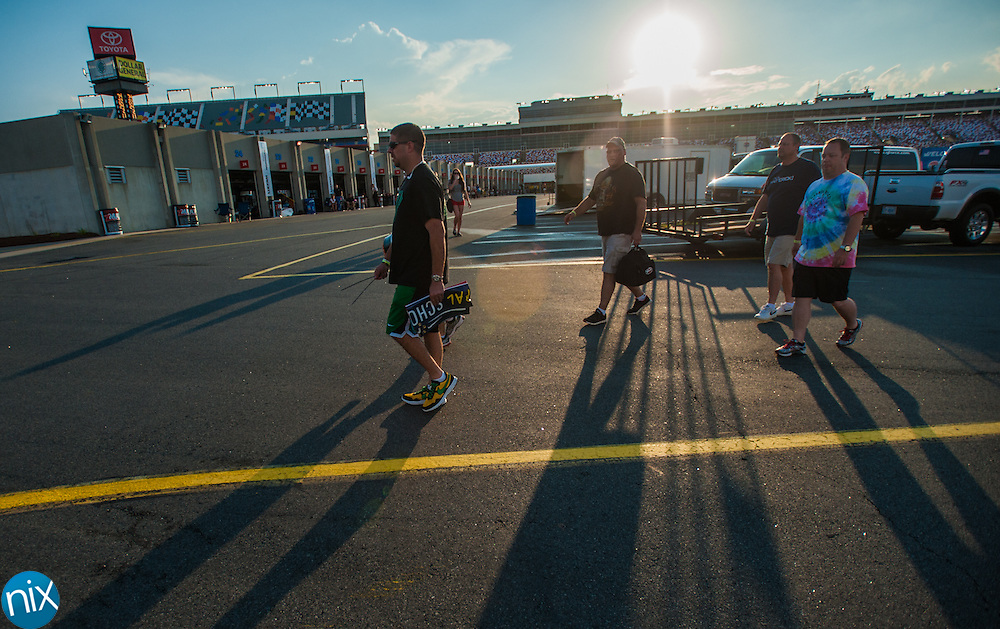 Principals from various Cabarrus County Schools walk through the garages on their way to their school buses prior to the Principal School Bus Slobberknocker at Charlotte Motor Speedway Tuesday night during the Summer Shootout.