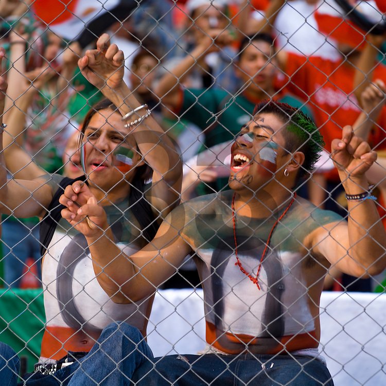 Mexican soccer fans or futbol fans cheer on their national team