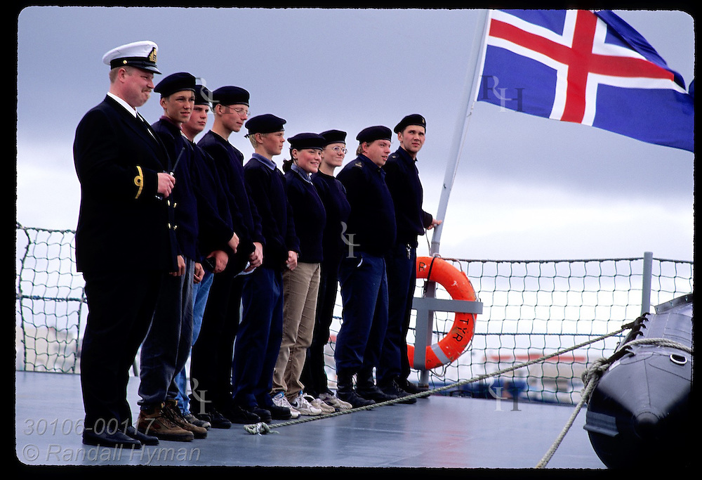Coast guard cadets stand at attention beside three crew members and flag as Tyr leaves port; Rvk Iceland
