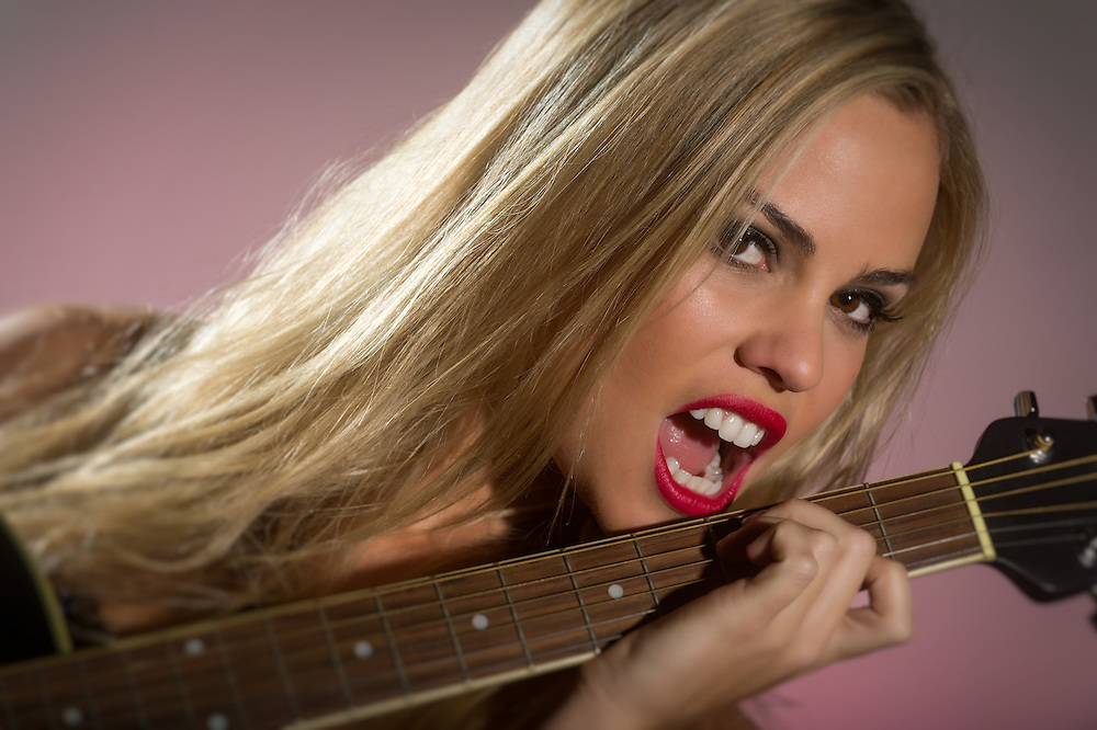 Rocker woman holding electric guitar in a close up shot