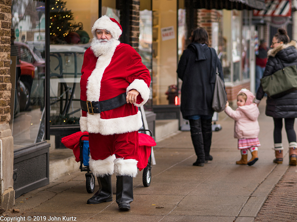 """30 NOVEMBER 2019 - WEST DES MOINES, IOWA: SANTA CLAUS walks down 5th Street, the main business street in West Des Moines, Saturday. He was handing out gifts to children on Small Business Saturday. """"Small Business Saturday"""" was first observed in the United States on November 27, 2010, as a counterpart to Black Friday and Cyber Monday, which are generally considered events at malls, """"big box"""" stores and e-commerce retailers. Small Business Saturday encourages holiday shoppers to patronize brick and mortar businesses that are small and local. Small Business Saturday is a registered trademark of American Express.      PHOTO BY JACK KURTZ"""