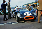 """Blurry photo of British Sports racing driver Bill de Selincourt (1921-2014) driving Lister-Jaguar """" Knobbly"""" car 33, BARC event Goodwood, March 1961 on starting line"""