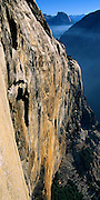 This is a view looking east down the 2,000 foot overhanging granite monolith, the SE face of El Capitan in Yosemite Valley, Yosemite National Park, from a climbing route called The Tempest. Half Dome is visible in the distance.