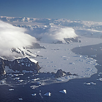 ANTARCTICA. Icebergs and pack ice in southern ocean below mountains and glaciers of Antarctic Peninsula.
