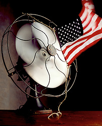Antique General electric oscillating fan with American flag tied to front of fan making the flag fly