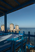 Restaurant overlooking calm blue sea with famous historical stone windmills at Tampakika, Chios, Greece