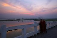 Two Buddhist monks chat as they watch the sun set on U Bien's Bridge near Mandalay, Myanmar (Burma).