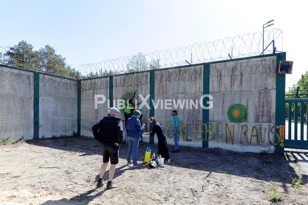 """Wendländische Atomkraftgegner/-innen sprühen ihre Botschaft an die Bundesgesellschaft für Endlagerung auf ein Reststück der Mauer, die das so genannte Erkundungsbergwerk in Gorleben jahrzehntelang hermetisch abgeriegelt hatte. Der Spruch """"Gorleben raus""""!"""" bezieht sich auf ihre Forderung, den Salzstock im Wendland mit der Vorstellung des """"Zwischenberichts Teilgebiete"""" im Herbst 2020 aus dem Verfahren der Endlagersuche zu nehmen. Beim Abriss der Mauer 2019 ist ein Stück als Mahnmal stehen geblieben. Rechtliche Querelen verhindern aber noch den freien Zugang, so dass die Atomkraftgegner/-innen Leitern zum Überwinden des Zauns mitbrachten.<br /> <br /> Ort: Gorleben<br /> Copyright: Andreas Conradt<br /> Quelle: PubliXviewinG"""