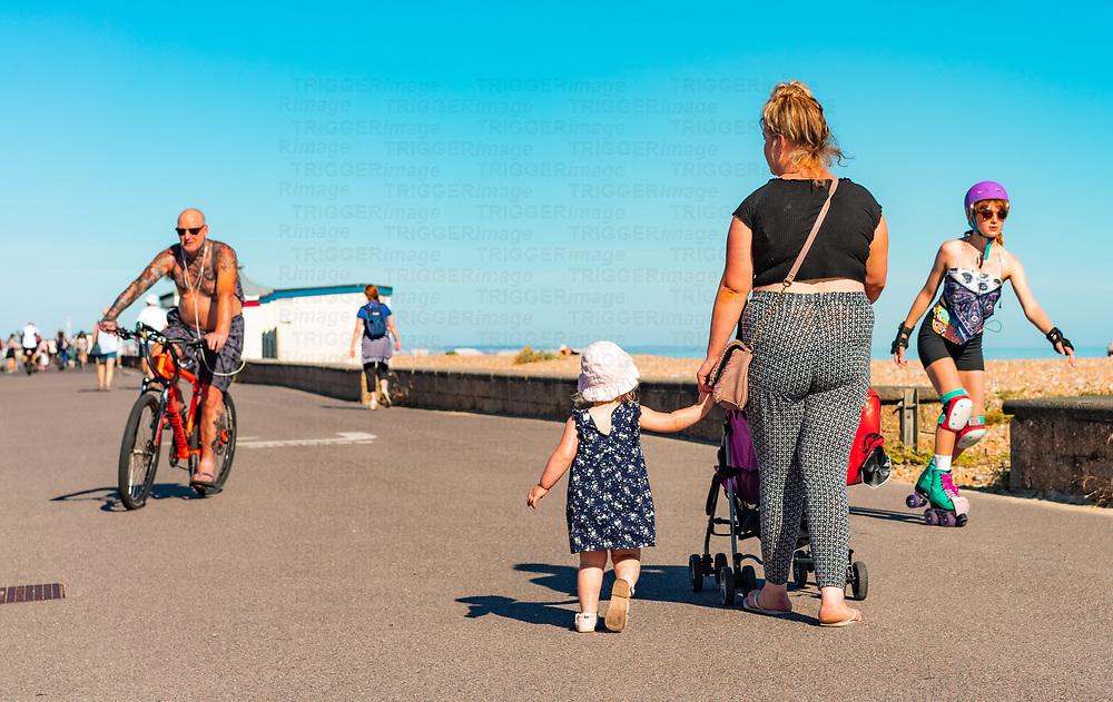 Mother and child on Worthing promenade in summer under blue sky on a summers days with cyclist and roller skating female teenager