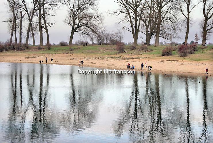 Nederland, Ooij, 20-12-2020Op deze zondag in de tweede lockdown zijn veel mensen buiten aan de wandel . Hier langs de Waal en de bizonbaai. De bizonbaai is een voormalig zandwingat, recreatieplas, waterplas, meertje, baai, langs de rivier de Waal. Onderdeel van staatsbosbeheer. Op de zomerdijk staan grote hoge bomen.Foto: ANP/ Hollandse Hoogte/ Flip Franssen