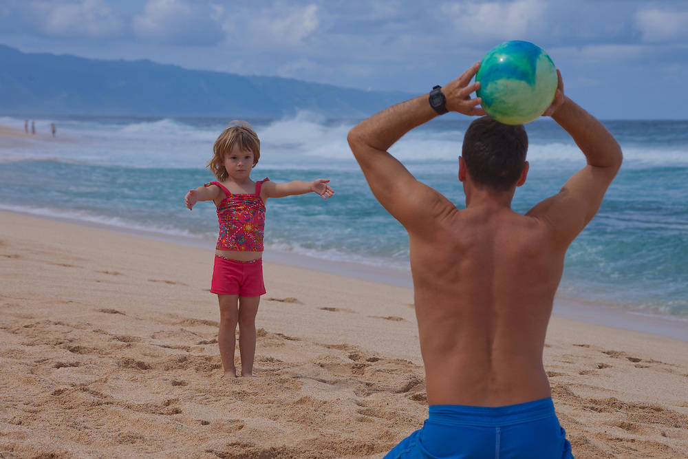 A little girl waits for her father to throw the ball on the beach in Hawaii