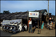 A man stands in front of a parking lot shelter in Hue, Vietnam, Southeast Asia, 1997