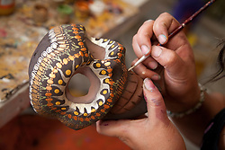 "North America, Mexico, Oaxaca Province, Arrazola, hands painting design on  skull ""alebrije"" made of copal wood"