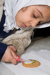 Pupil at the Nottingham Islamia school decorating a biscuit for the Eid Fair,