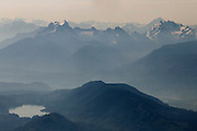 Thick haze fills the valley between Lake Cavanaugh and the mountains of the North Cascades in this aerial view over Skagit County, Washington. Among the prominent peaks visible are Whitehorse Mountain (center left) and Three Fingers Mountain (center right).