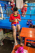 23 DECEMBER 2014 - BANGKOK, THAILAND:  A boxer unrolls tape for his hands before sparring at the Kanisorn gym in Bangkok. The Kanisorn boxing gym is a small gym along the Wong Wian Yai - Samut Sakhon train tracks. Young people from the nearby communities come to the gym to learn Thai boxing. Muay Thai (Muai Thai) is a mixed martial art developed in Thailand. Muay Thai became widespread internationally in the twentieth century, when Thai boxers defeated other well known boxers. A professional league is governed by the World Muay Thai Council. Muay Thai is frequently seen as a way out of poverty for young Thais. Muay Thai professionals and champions are often celebrities in Thailand.    PHOTO BY JACK KURTZ