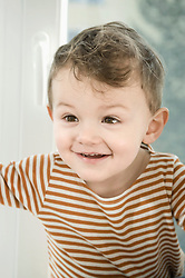 Boy playing with curtain, smiling