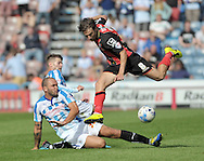 Joel Lynch of Huddersfield Town slides in on Harry Arter of Bournemouth during the Sky Bet Championship match at the John Smiths Stadium, Huddersfield<br /> Picture by Graham Crowther/Focus Images Ltd +44 7763 140036<br /> 09/08/2014