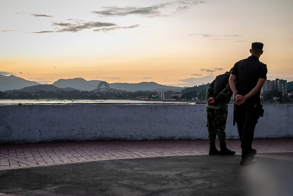 Panama City, Panama - December 22, 2008: Two security personel walk at sunset in the historic district of Casco Viejo in Panama City. In the distance on the left is the Bridge of the Americas (Puente de las Américas), which spans the Pacific entrance to the Panama Canal.