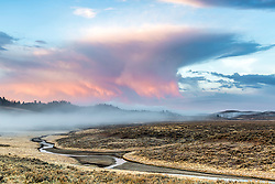 Allum Creek Sunrise, a morning thunderstorm provides a reflective canvas for light in the western sky of Yellowstone National Park