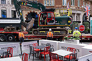 Construction work banksmen contractors oversee the loading of a tracked excavator on to a low-loader in Leicester Square in the West End, on 14th October, 2021, in Westminster, London, England.