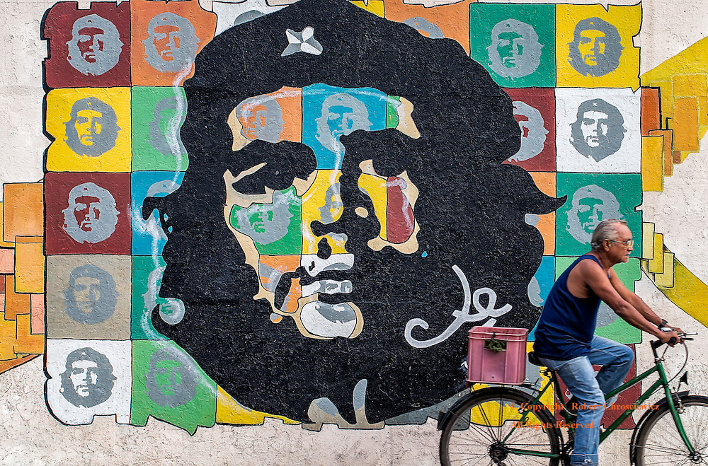 Propaganda of the People: The diverging  path of a nation from its past can be symbolically seen as a man cycles towards his daily chores, past a large colourful wall painting of Che Guevara - the dated, first man of propaganda, Havana Cuba.