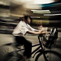 Boy biking home from school,  French Quarter, Hanoi