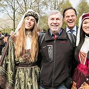 NLD/Lisse/20190417 - Minister Rutte doopt tulp inde Keukenhof, Minister Rutte springt achter een toerist die op de foto gaat met bloemenmeisjes